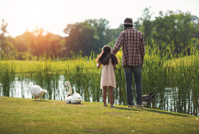 Mind-Your-Mental-Well-Being-in-Times-of-Uncertainty_Father and daughter by river with geese